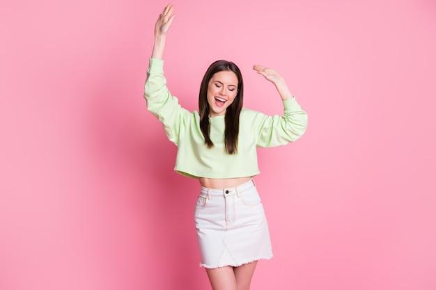 Photo de jolie jolie dame lever les bras danse soirée disco silhouette mince danseur excité porter décontracté pull vert récolte ventre nu jeans jupe courte isolé fond de couleur pastel rose