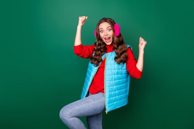 Photo de jolie jolie jeune femme bouche ouverte regard étonné fou lever les poings genou gagner équipe bataille de boules de neige porter des jeans chauffe-oreilles roses gilet bleu sweat-shirt rouge isolé fond de couleur verte