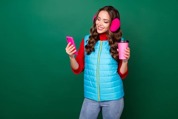 Photo d'une jolie jolie jeune femme tenant une tasse de café à emporter écran de téléphone souriant partager après porter des cache-oreilles roses gilet zippé bleu pull rouge jeans isolé fond de couleur verte