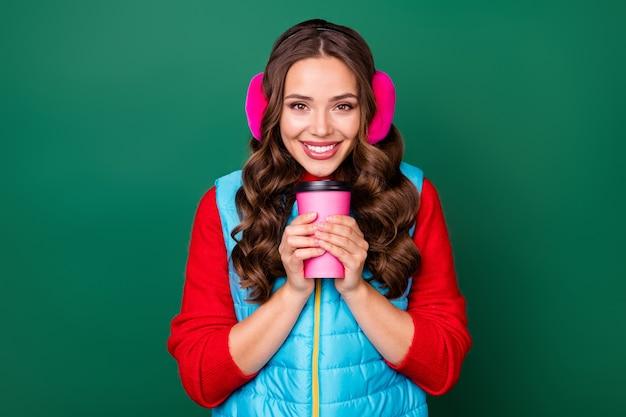 Photo d'une jolie jolie jeune femme tenant une tasse de café à emporter rayonnante souriante faire une pause après le travail porter des chauffe-oreilles roses gilet bleu pull rouge isolé fond de couleur verte