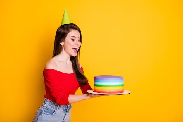 Photo de jolie jolie jeune fille étonnée bouche ouverte tenir gâteau surprise look fête d'anniversaire porter cône chemise épaules ouvertes jupe en jean isolé fond de couleur jaune vif