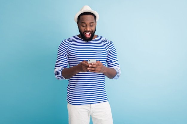 Photo de jolie peau sombre guy voyageur bonne humeur tenir l'application téléphone navigation chatter amis porter bonnet de soleil blanc chemise de marin rayé shorts mur de couleur bleu isolé