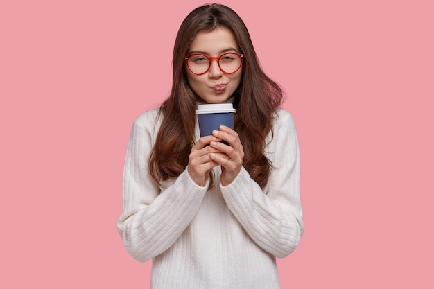 Photo d'une jolie petite amie a l'intention de faire quelque chose, regarde scrupuleusement, porte des lunettes pour une bonne vision, boit du café dans une tasse en papier