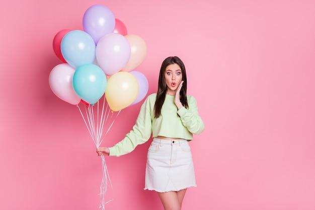 Photo de jolies amies choquées organisent une fête d'anniversaire surprise de nombreux ballons à air usure inattendue pull vert décontracté jeans mini jupe isolé fond de couleur pastel rose