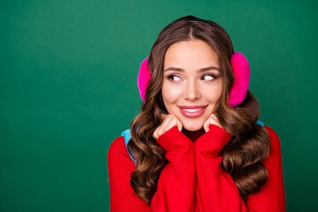 Photo de jolies mains de jeune femme rêveuse tenant le visage rayonnant de sourire regard espace vide en attente de livraison de café porter des cache-oreilles roses gilet bleu pull rouge isolé fond de couleur verte
