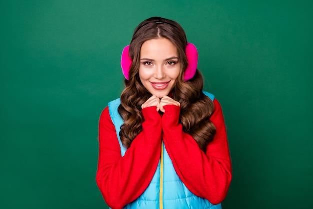 Photo de jolies mains de jeune femme tenant le visage rayonnant souriant regard affectueux garder au chaud froid vêtements de soirée d'hiver chauffe-oreilles rose gilet bleu pull rouge isolé fond de couleur verte