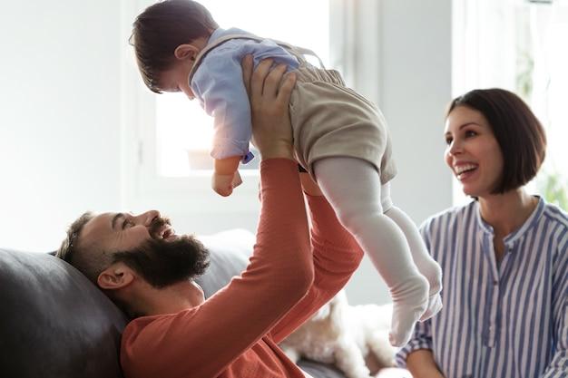 Photo de jolis jeunes parents avec leur bébé jouant sur un canapé à la maison.