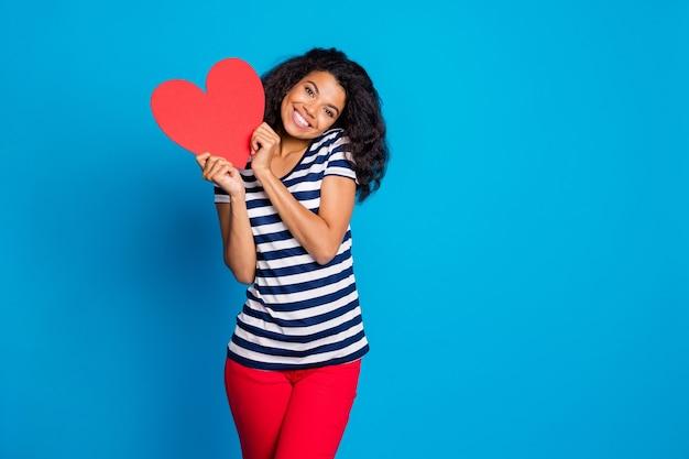 Photo de joyeuse belle jolie femme tenant une carte postale grand coeur rouge