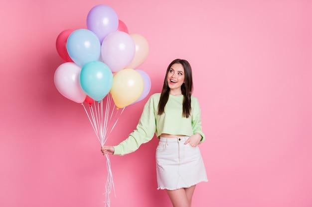 Photo de joyeuse charmante dame organiser une fête d'anniversaire surprise meilleur ami tenir de nombreux ballons à air porter des jeans pull vert décontracté mini jupe isolé fond de couleur pastel rose