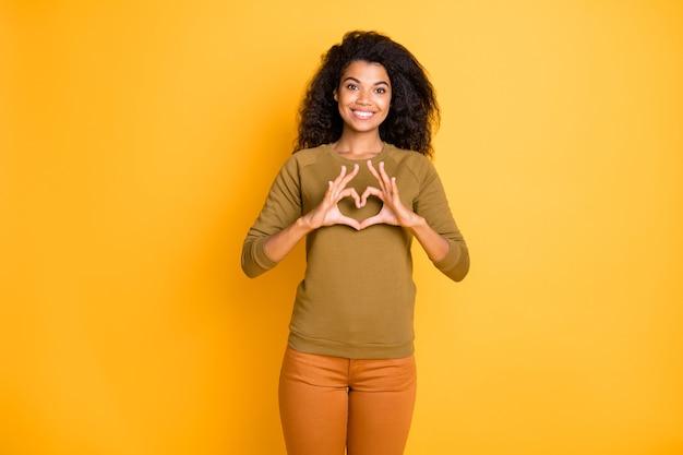 Photo de joyeuse charmante jolie jolie femme noire affectueuse vous montrant en forme de coeur portant un pantalon pantalon orange démontrant son amour isolé sur fond de couleur vive