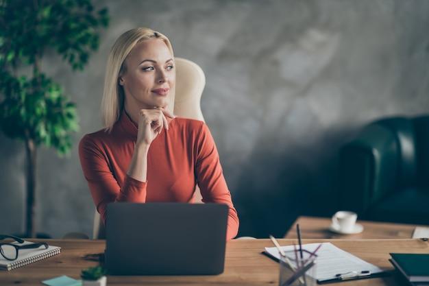 Photo de joyeuse femme rêveuse mignonne à la recherche de loin à la recherche de nouvelles idées pour le démarrage assis à table avec un ordinateur portable dessus