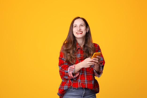 Photo de joyeuse jeune femme en chemise à carreaux tenant un smartphone