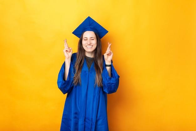 Photo de joyeuse jeune femme diplômée et croisant les doigts