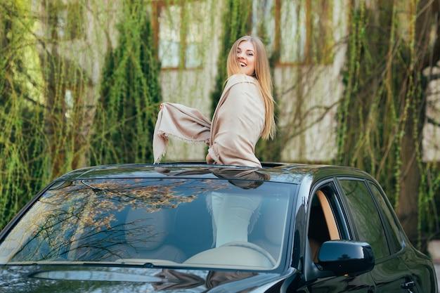 Photo de joyeuse jeune femme portant des lunettes de soleil et les mains levées sur le toit ouvrant de la voiture de luxe