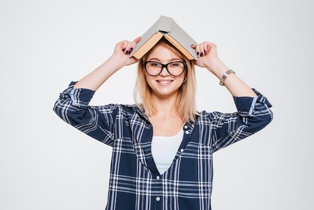 Photo de joyeuse jeune femme tenant un livre isolé sur fond blanc.