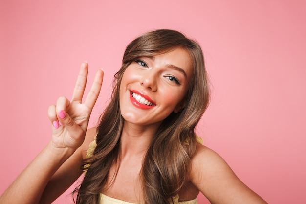 Photo de joyeuse jolie femme des années 20 avec de longs cheveux bruns souriant et montrant le signe de la victoire à la caméra tout en prenant selfie sur téléphone mobile, isolé sur fond rose