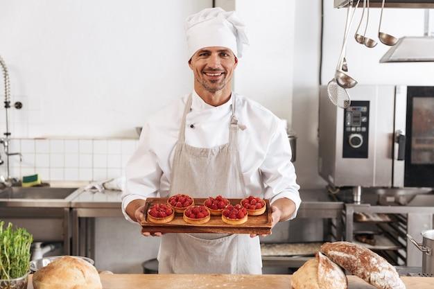 Photo de joyeux chef masculin en uniforme blanc tenant la plaque avec des gâteaux
