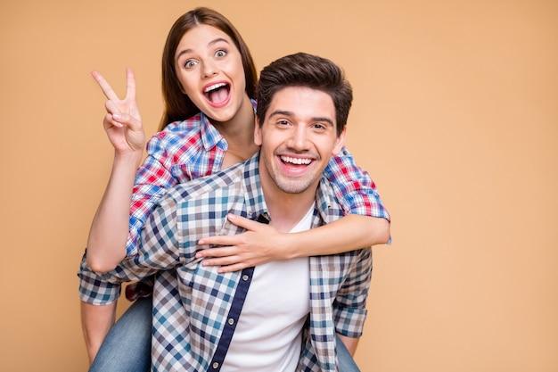 Photo de joyeux copain fou excité positif et petite amie avec elle vous montrant v-sign avec une expression faciale excitée et lui tenant son ferroutage isolé sur fond de couleur pastel beige