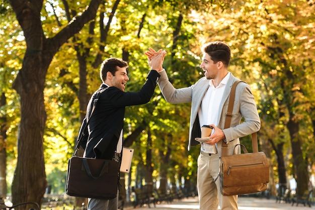 Photo de joyeux entrepreneurs en costumes marchant en plein air à travers le parc verdoyant avec café à emporter et ordinateur portable, pendant la journée ensoleillée