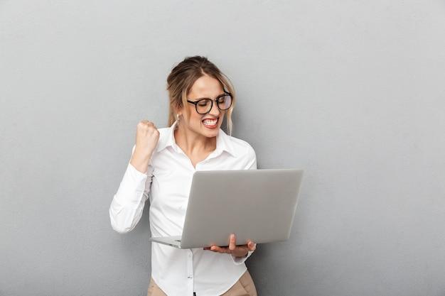Photo de joyeux femme d'affaires portant des lunettes debout et tenant un ordinateur portable au bureau, isolé
