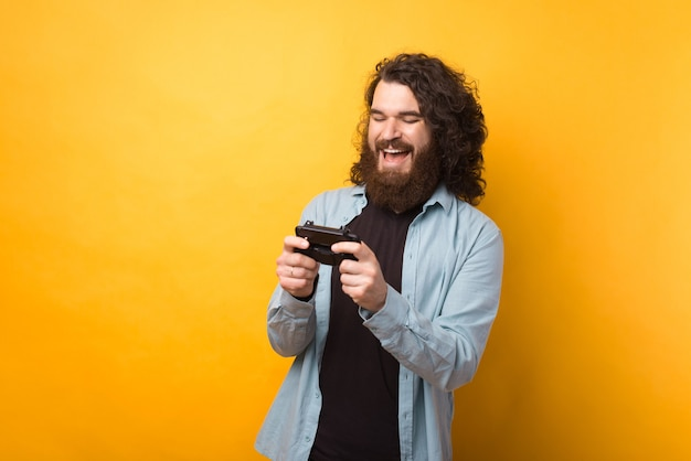 Photo de joyeux jeune homme barbu jouant à des jeux sur smartphone sur fond jaune