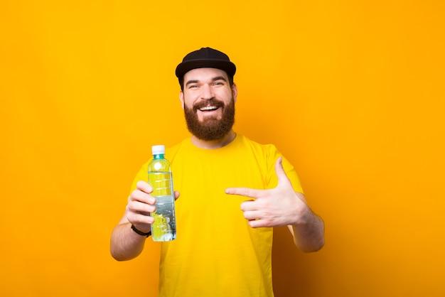Photo de joyeux jeune homme pointant sur une bouteille d'eau fraîche, boire de l'eau tous les jours
