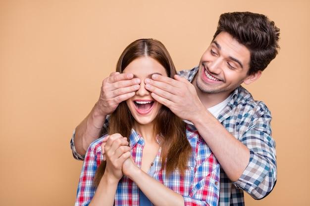 Photo de joyeux joli joli couple fascinant magnifique avec lui couvrant ses yeux et son extatique et à la tentation de la surprise à venir isolée sur fond de couleur pastel beige
