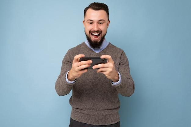 Photo de joyeux joyeux beau jeune homme brune mal rasé avec une barbe portant un pull gris de tous les jours et une chemise bleue isolée sur un mur de fond tenant un smartphone jouant à des jeux via un téléphone portable à la recherche