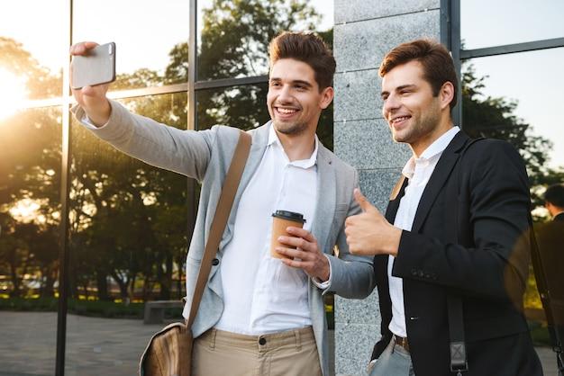 Photo de joyeux partenaires commerciaux en costume à l'aide de smartphones pour selfie, debout à l'extérieur près du bâtiment avec du café à emporter