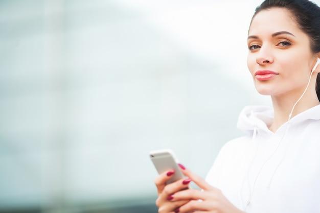 Photo de joyful fitness femme des années 30 dans les vêtements de sport toucher une oreille bluetooth et tenir un téléphone portable tout en se reposant dans le parc verdoyant
