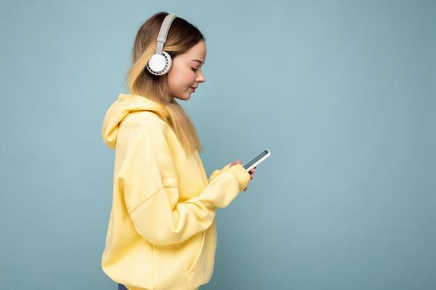 Photo latérale d'une belle jeune femme portant une tenue décontractée élégante isolée sur colorée