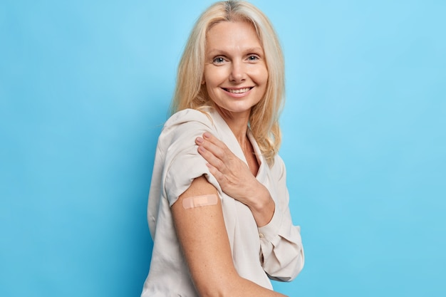 Une photo latérale d'une femme blonde de quarante ans approuve la campagne de vaccination et reçoit l'inoculation du virus covid 19 se sent protégée isolée sur le mur bleu