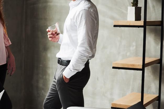 Photo latérale d'un homme au bureau portant un verre avec de l'alcool. fille à gauche.