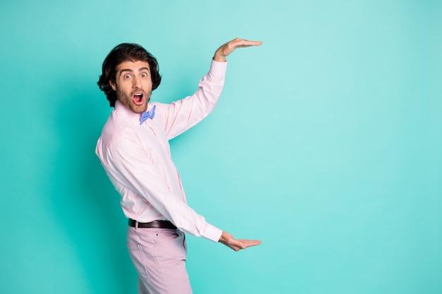 Photo latérale d'un homme aux cheveux ondulés bruns portant une tenue rose mesure l'espace vide deux mains isolées sur fond de couleur sarcelle