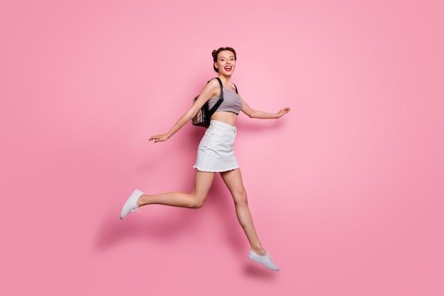 Photo latérale de profil pleine longueur de fille candide jump run amusez-vous sur le voyage de printemps porter des baskets de vêtements gris moderne sac à dos isolé sur couleur rose
