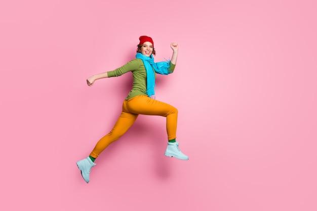 Photo latérale de profil pleine longueur de joyeuse fille excitée chanceuse sauter courir après les remises de saison porter des chaussures couvre-chef bleu rouge isolé sur mur de couleur rose