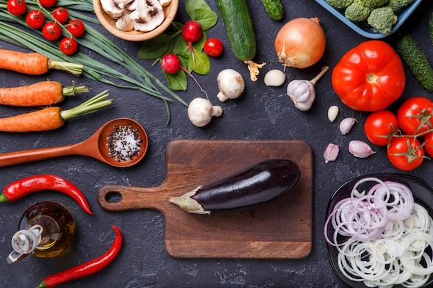 Photo sur des légumes frais, des champignons, une planche à découper, du beurre, un couteau, des aubergines