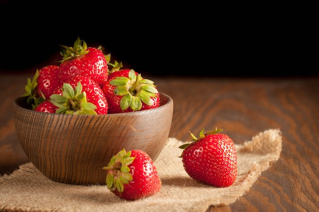 Photo macro de fraise rouge mûre fraîche dans un bol en bois sur fond rustique. produits naturels biologiques.