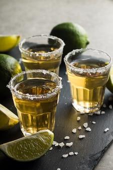 Photo macro de plans de tequila mexicaine d'or avec de la chaux et du sel sur fond rustique en bois. concept de boisson alcoolisée. mise au point sélective.