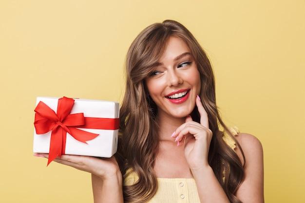 Photo de magnifique fille européenne des années 20 ayant de longs cheveux bruns souriant et ce qui est à l'intérieur de la boîte-cadeau allongé à sa paume, isolé sur fond jaune