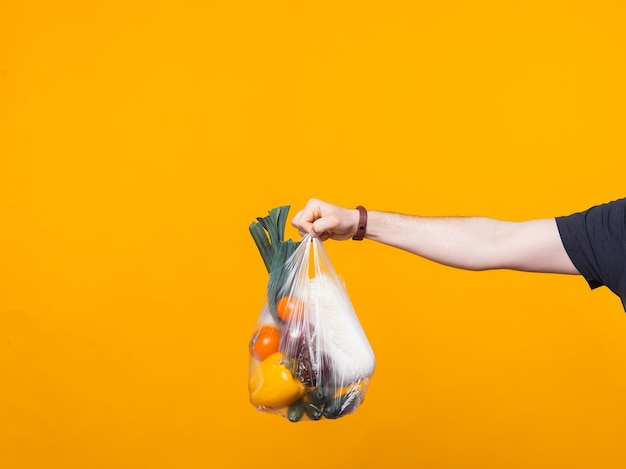 Photo d'une main d'homme tenant une pochette d'épicerie près d'un mur jaune