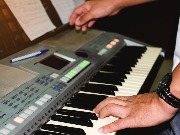 Photo de main de jeune homme jouant du piano électrique.