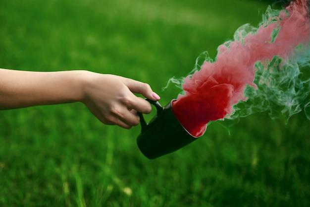 Photo de la main avec une tasse et de la fumée rouge