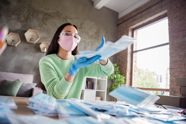 Photo de mains d'une femme d'affaires asiatique jetant des masques médicaux contre la grippe faciale gratuits livraison généreuse de respirateurs de sécurité antivirale dans un sac à fermeture éclair rester bureau à domicile à l'intérieur