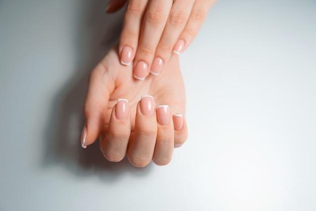 Une photo de mains montrant leurs ongles, ongles français