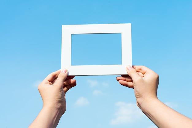 Photo de mains tenant des cadres photo sur fond de ciel bleu