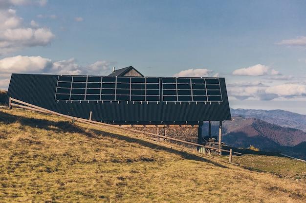 Photo d'une maison dans les montagnes, sur le toit d'un panneau solaire, coucher de soleil