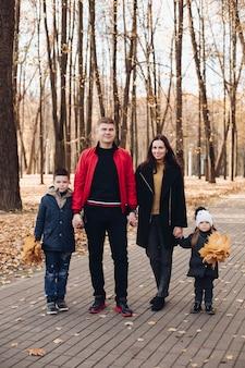 Photo de maman aux longs cheveux noirs en manteau noir, papa aux cheveux courts en veste rouge, joli petit garçon avec sa jeune sœur tenant des bouquets de feuilles d'automne