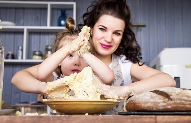 Photo de maman et fille cuisinent ensemble dans la cuisine
