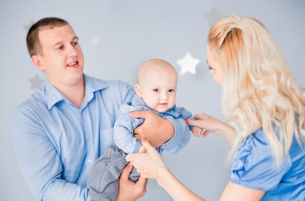 Photo de maman et papa jouent avec le bébé en train de le vomir